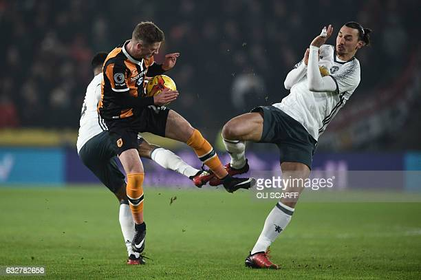 Manchester United's Swedish striker Zlatan Ibrahimovic is blocked by Hull City's English defender Josh Tymon during the EFL Cup semifinal secondleg...