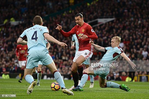 Manchester United's Swedish striker Zlatan Ibrahimovic is tackled by Burnley's English defender Ben Mee on the edge of the box during the English...