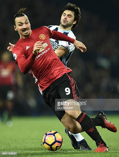 Manchester United's Swedish striker Zlatan Ibrahimovic is tackled by West Bromwich Albion's Argentinian midfielder Claudio Yacob during the English...