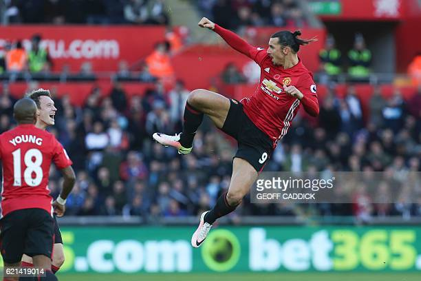 Manchester United's Swedish striker Zlatan Ibrahimovic jumps and kicks the air as he celebrates scoring his team's second goal with Manchester...