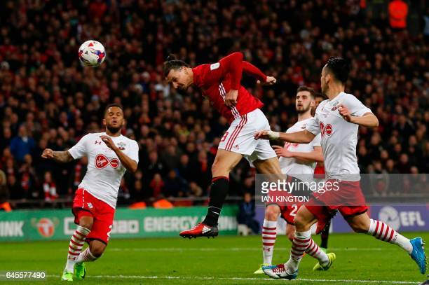TOPSHOT Manchester United's Swedish striker Zlatan Ibrahimovic jumps to head their third goal during the English League Cup final football match...