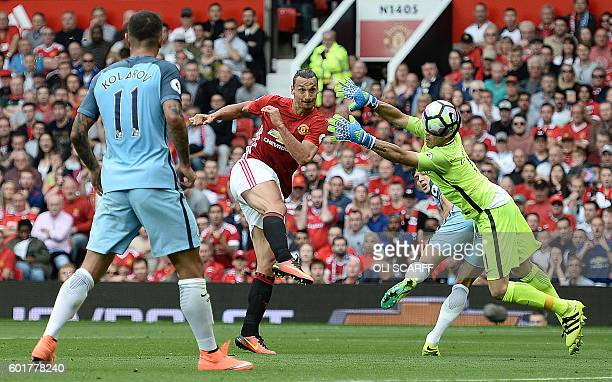 Manchester United's Swedish striker Zlatan Ibrahimovic shoots past Manchester City's Chilean goalkeeper Claudio Bravo to score their first goal...