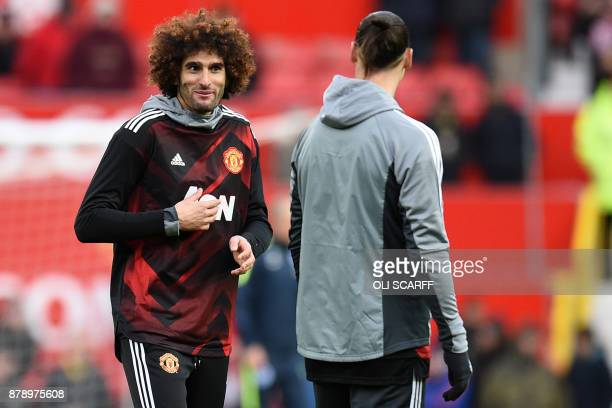 Manchester United's Swedish striker Zlatan Ibrahimovic warms up with Manchester United's Belgian midfielder Marouane Fellaini ahead of the English...
