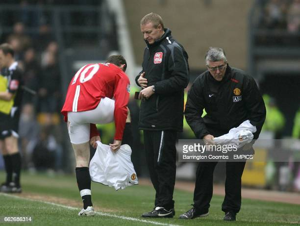 Manchester United's Wayne Rooney changes his shorts on the touchline after they were ripped during a challenge