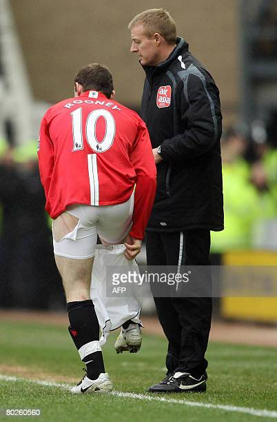 Manchester United's Wayne Rooney changes his torn shorts during an English Premier League football match against Derby County onMarch 15 2008 at...