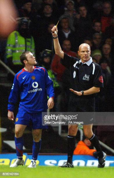Manchester United's Wayne Rooney looks to see what colour card he gets from referee Steve Bennett against West Ham United during the Barclays...