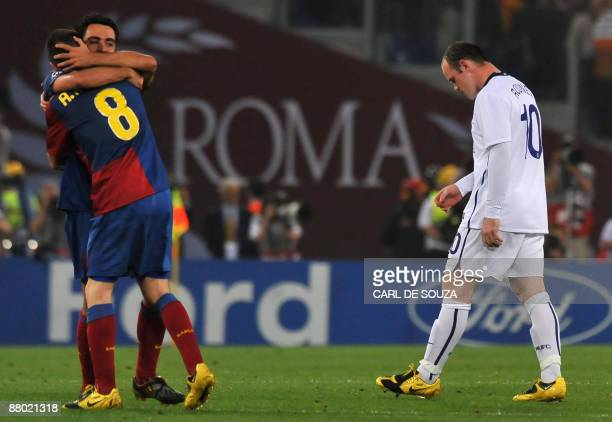 Manchester United's Wayne Rooney walks by as Barcelona's Xavi Hernandez and Andres Iniesta celebrate after winning the UEFA football Champions League...
