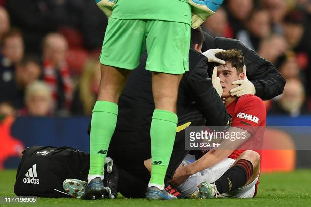 Manchester United's Welsh midfielder Daniel James receives medical attention after picking up an injury during the English Premier League football...