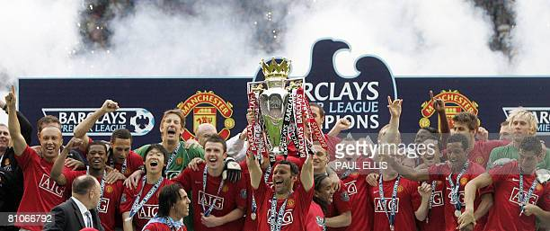 Manchester United's Welsh midfielder Ryan Giggs lifts the Premier League trophy after beating Wigan Athletic in their English Premier League football...