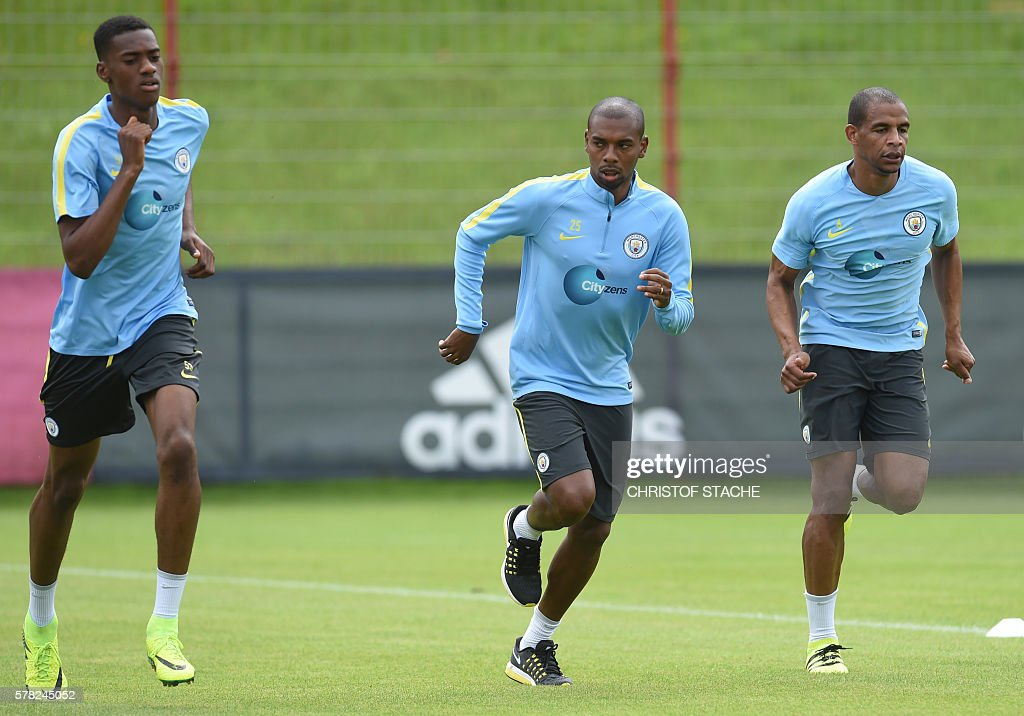 Manchester's midfielder Tosin Adarabioyo, Manchester's Brazilian midfielder Fernandinho Roza and Manchester's Brazilian midfilder Fernando run during a training session of Manchester City at the training ground of the German first division football team FC Bayern Munich in Munich, on July 21, 2016. / AFP / CHRISTOF
