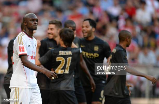 Manchester's players celebrate a goal while Milan's Bakaye Traore looks on during the Audi Cup soccer semifinal match Manchester City vs AC Milan at...