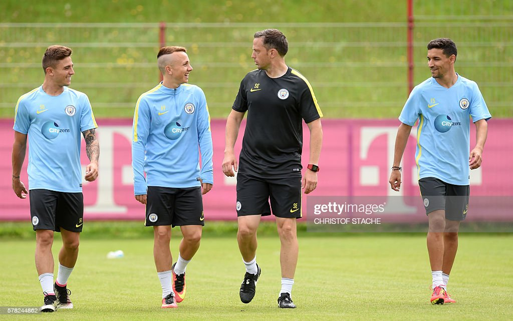 Manchester's Spanish defender Pablo Maffeo (L), Manchester's Spanish defender Angelino Tasende (2ndL) and Manchester's Spanish midfielder Jesus Navas (R) joke with a assistent coach during a team training session of Manchester City at the training ground of the German first division football team FC Bayern Munich in Munich, on July 21, 2016. / AFP / CHRISTOF
