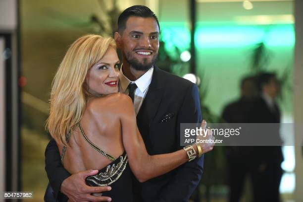 Manchester's United goalkeeper Argentinian Sergio Romero poses with his wife on a red carpet during Argentine football star Lionel Messi and...