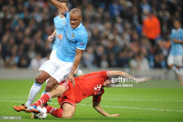 Manchester's Vincent Kompany vies for the ball with Munich's Thomas Mueller during the Champions League Group D match between ManchesterCity and...