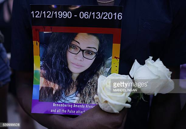 A mand holds a portrait of a victim of the Pulse nightclub shooting at a vigil for the victims of the Pulse nightclub shooting on June 13 2016 at the...