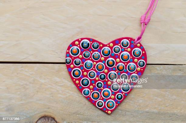 Mandala with heart shape on wooden background