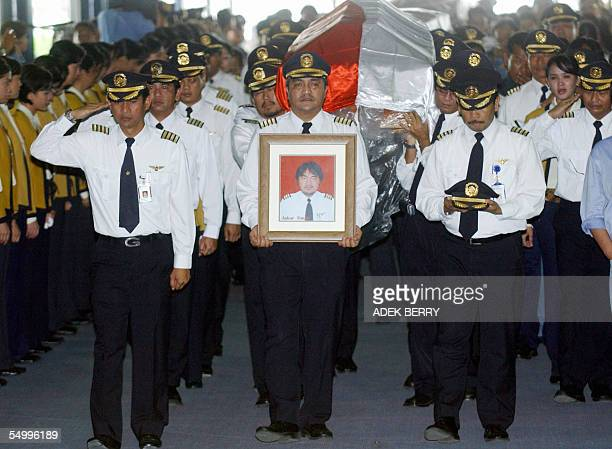Mandala's employees carry the coffin of pilot Askar Timur at an airport in Jakarta 06 September 2005 The Mandala Airlines jetliner crashed just after...