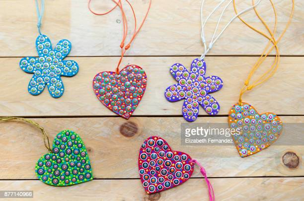 Mandalas with flower and heart shapes on wooden background