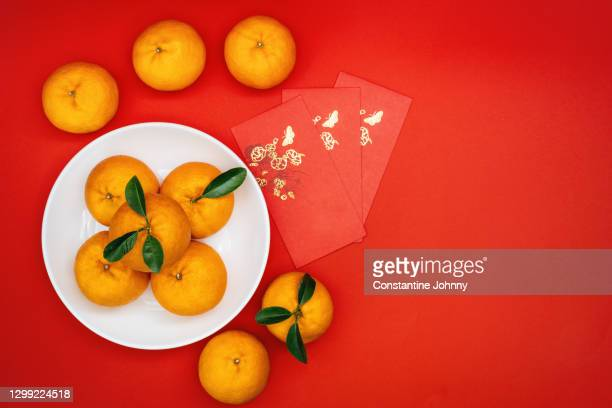 mandarin oranges and red envelope on red background. chinese new year. - chinese new year stock pictures, royalty-free photos & images