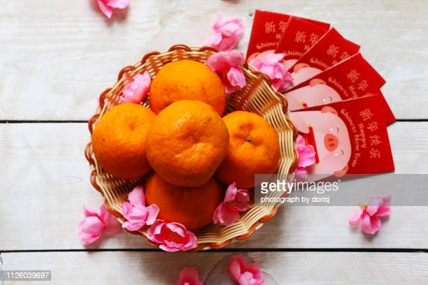 Mandarin oranges in basket with Chinese New Year red packets