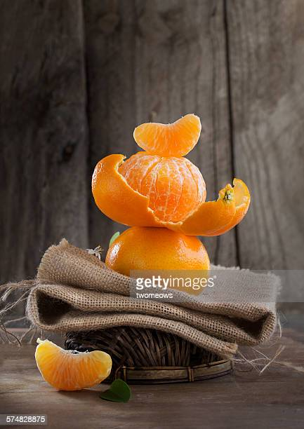 Mandarin oranges on moody rustic wooden table to