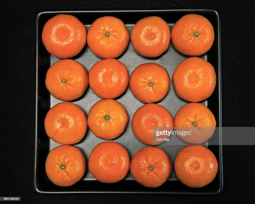 Mandarine orange (citrus reticulata) fruits arranged side by side on black tray : Stock-Foto