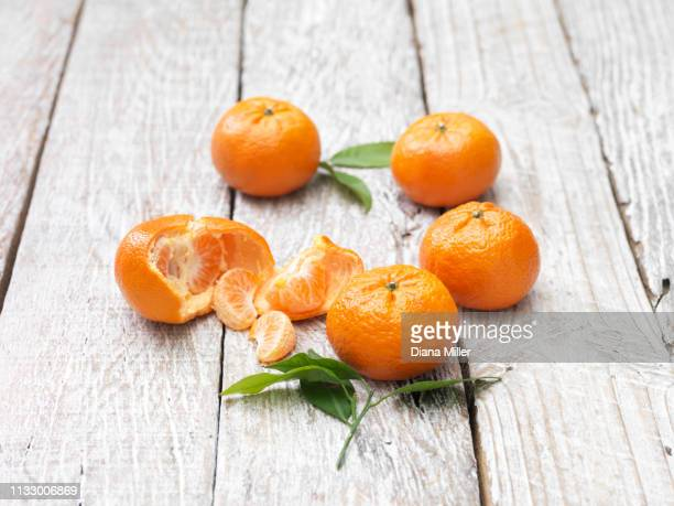 mandarins peeled and whole on whitewashed wooden table - whitewashed stock pictures, royalty-free photos & images