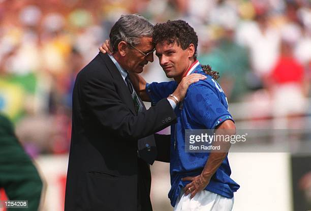 OF ITALY IS CONSOLED BY A TEAM OFFICIAL AFTER HE MISSED THE DECISIVE PENALTY IN THE PENALTY SHOOTOUT ALLOWING BRAZIL TO WIN THE 1994 WORLD CUP FINAL...