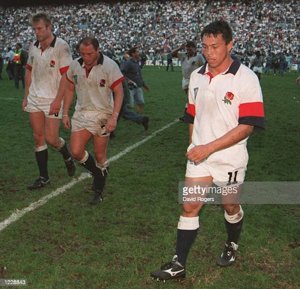 BRIAN MOORE AND TIM RODBER HANG THEIR HEADS IN DEJECTION AS THEY WALK OFF THE PITCH AFTER LOSING TO NEW ZEALAND IN THE SECOND RUGBY WORLD CUP...