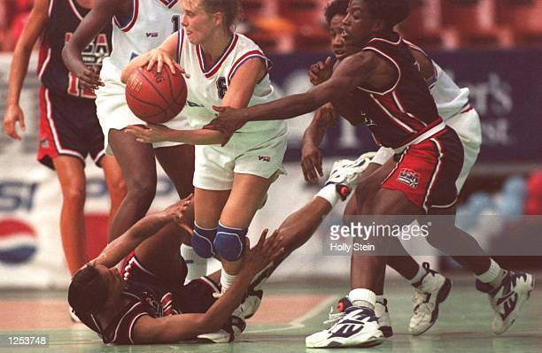 AS SHE HOLDS ON TO THE ARM OF YANNICK SOUVRE OF FRANCE WHO IS TRYING TO PASS THE BALL AND STUMBLES OVER AN UNIDENTIFIED USA PLAYER WHO HAS FALLEN ON...