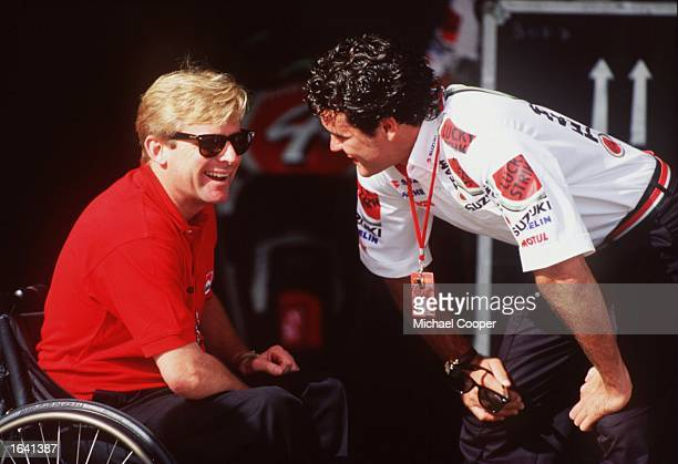 ENJOYS A JOKE WITH THREE TIMES FORMER 500CC WORLD CHAMPION WAYNE RAINEY PRIOR TO PRACTICE IN THE1995 AUSTRALIAN MOTORCYCLE GRAND PRIX AT EASTERN...