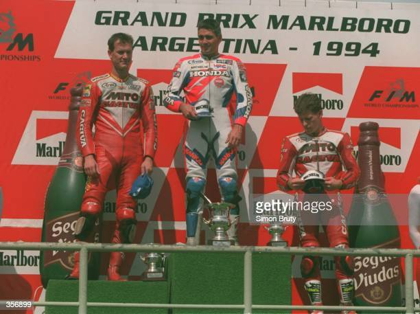 IS FLANKED BY SECOND PLACED DOUG CHANDLER OF THE USA THIRD PLACED JOHN KOCINSKI OF THE USA ON THE PODIUM AFTER THE 1994 500CC ARGENTINIAN BIKE GRAND...