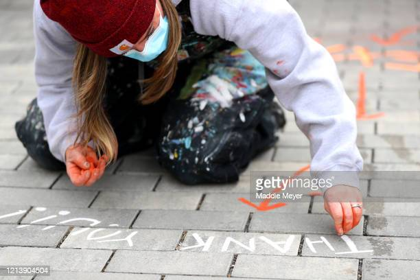 Mandee Martin of Somerville MA marks the walkway at the Safe Supply outdoor grocery store at Bow Market on March 21 2020 in Somerville Massachusetts...
