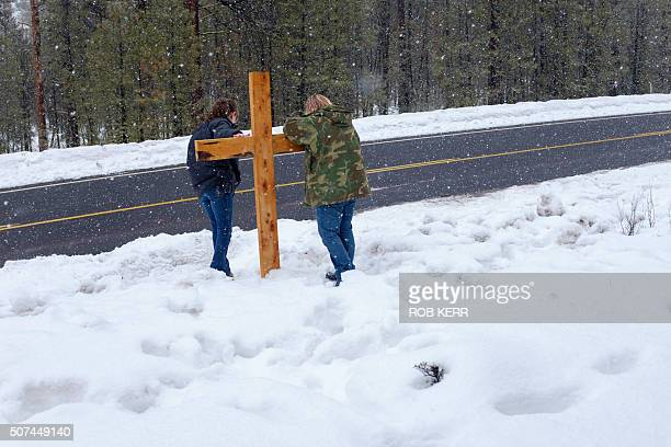 TOPSHOT Mandi Jacobs and Jenna Lynn react at a wooden cross on Highway 395 near Burns Oregon on January 29 at the location where Robert LaVoy Finicum...