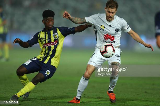 Mandi Sosa of Wellington Phoenix contests the ball with Charles M'Mombwa of the Central Coast Mariners during the round 21 ALeague match between the...