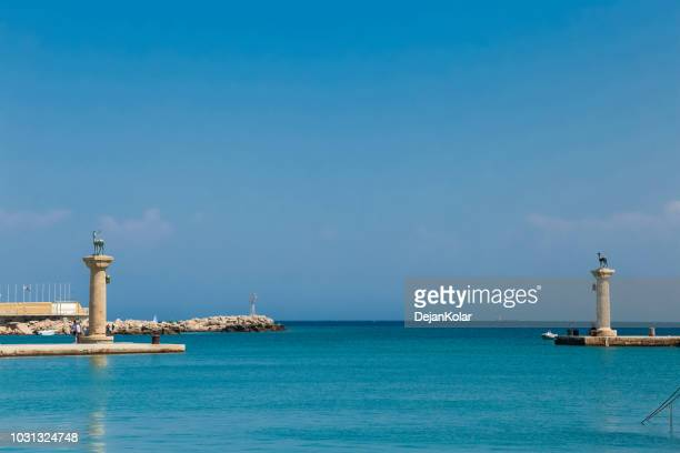 mandraki harbour, rhodes, greece - mandraki harbour entrance - colossus stock photos and pictures