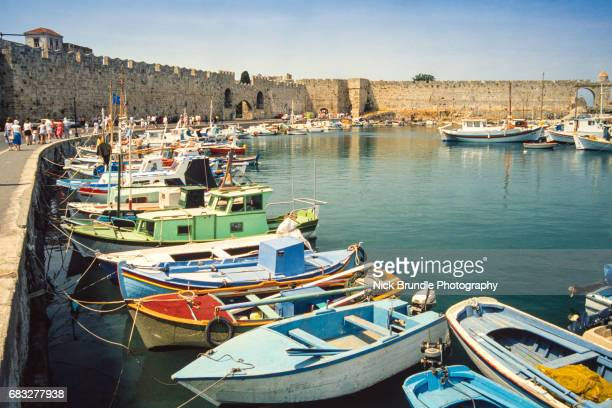 mandraki harbour, rhodes, greece - lindos stock photos and pictures