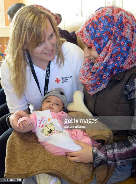 Mandy Baeumler team leader of the German Red Cross looks after Haya Diwabi from Syria and her threemonthold daughter in the Neue Messe refugee...