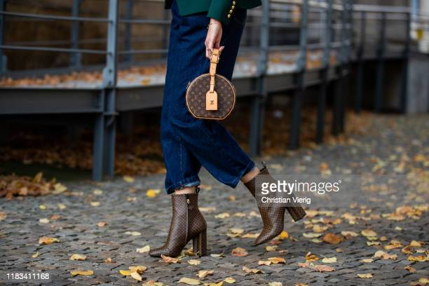 Mandy Bork is seen wearing brown Louis Vuitton ankle boots round Louis Vuitton bag dark denim jeans Zara on October 25 2019 in Berlin Germany