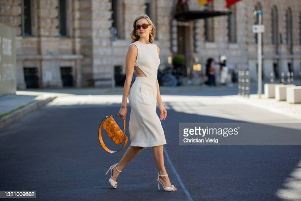 Mandy Bork is seen wearing creme white dress, sunglasses and orange bag Fendi, white heels Jimmy Choo on May 31, 2021 in Berlin, Germany.