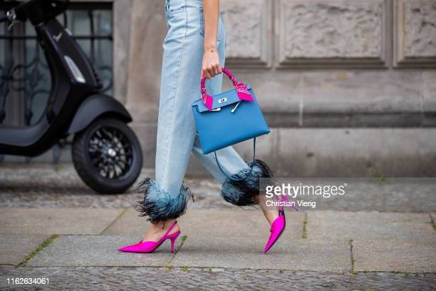 Mandy Bork is seen wearing denim jeans with feathers Prada, purple heels Balenciaga, Hermes bag on July 17, 2019 in Berlin, Germany.