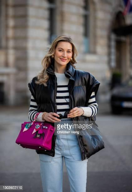 Mandy Bork is seen wearing light blue two tone denim jeans Bash, striped jumper Bash, Dior sneaker, Celine sunglasses, Hermes bag on February 24,...