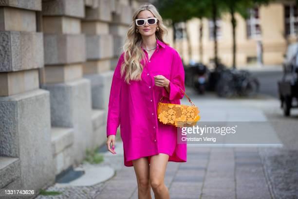 Mandy Bork is seen wearing pink button up Sezoona dress, Amina Muaddi heels, Linda Farrow sunglasses in white, orange Fendi bag on July 31, 2021 in...