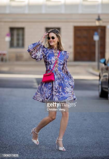 Mandy Bork is seen wearing purple dress with floral print Zimmermann, red bag Hermes, Linda Farrow sunglasses, Jimmy Choo heels on March 08, 2021 in...