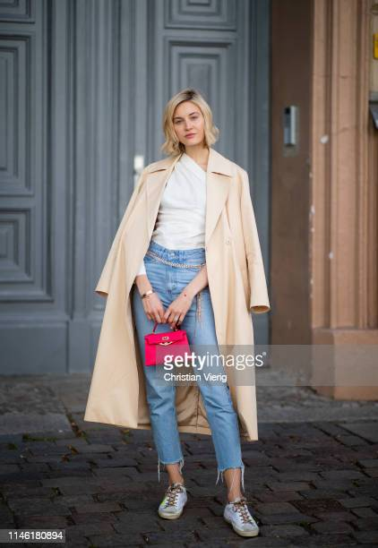 Mandy Bork is seen wearing white blouse Zara, cropped denim jeans Zara, red Hermes mini bag, beige &other stories trench coat, shoes Golden Goose,...