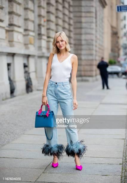 Mandy Bork is seen wearing white top Topshop, denim jeans with feathers Prada, purple heels Balenciaga, Hermes bag on July 17, 2019 in Berlin,...