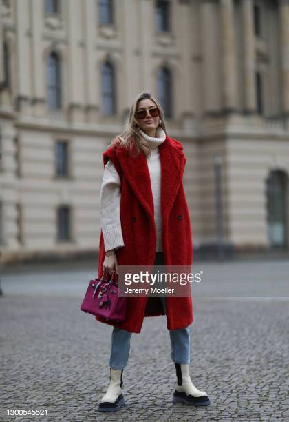 Mandy Bork wearing Bottega Veneta beige boots and shades, red Max Mara Teddy vest, Hermes bag, H&M beige sweater and Marco Polo blue jeans on...