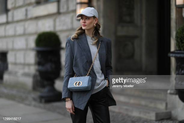 Mandy Bork wearing Dior grey bag, & other stories cap, grey blazer and sweater, Edited black leather pants on January 29, 2021 in Berlin, Germany.