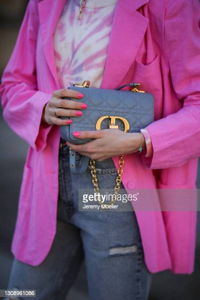 Mandy Bork wearing Philantrophy tie dye sweater, Zara destroyed jeans, pink Storets blazer and blue Dior bag on March 22, 2021 in Berlin, Germany.