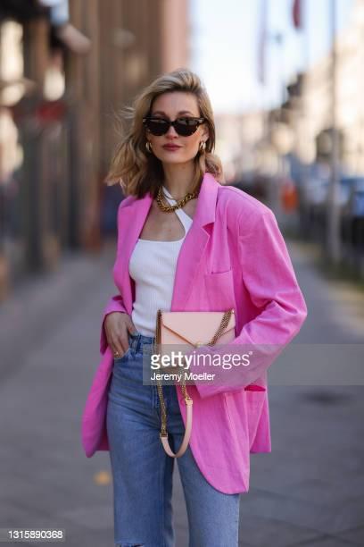 Mandy Bork wearing Zara destroyed blue jeans, white Zimmermann top, rose Bulgari bag, Bottega Veneta shades and pink Storets blazer on April 27, 2021...